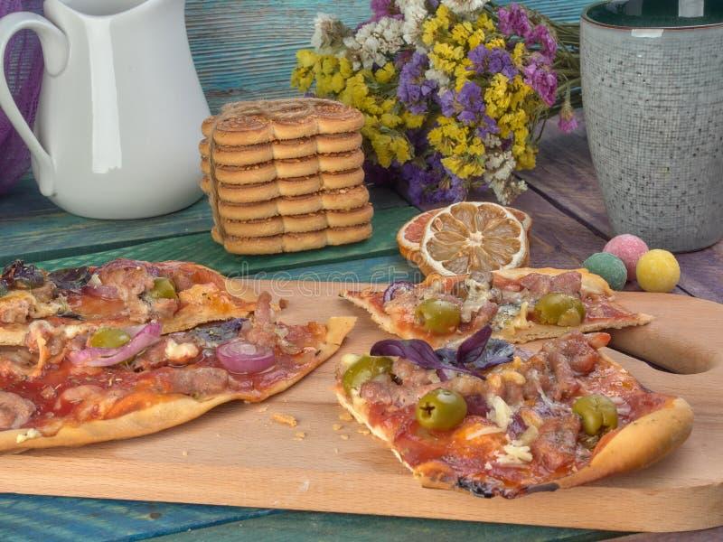 Pizza auf dünnem Teig Mit Scheiben der Salami und des Schinkens, der Oliven und der Tomaten lizenzfreies stockfoto