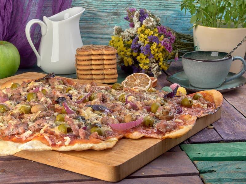 Pizza auf dünnem Teig Mit Scheiben der Salami und des Schinkens, der Oliven und der Tomaten lizenzfreies stockbild