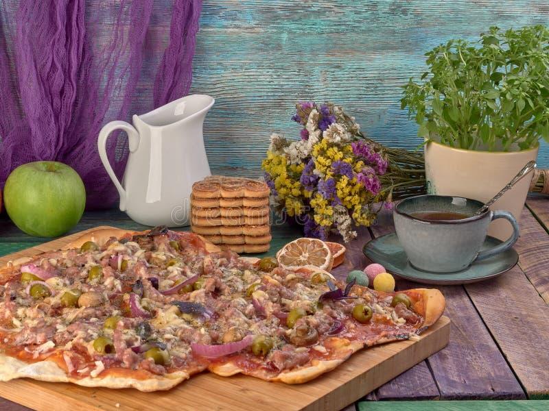Pizza auf dünnem Teig Mit Scheiben der Salami und des Schinkens, der Oliven und der Tomaten lizenzfreie stockfotografie