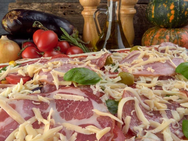 Pizza auf dünnem Teig Mit Scheiben der Salami und des Schinkens, der Oliven und der Tomaten stockbilder