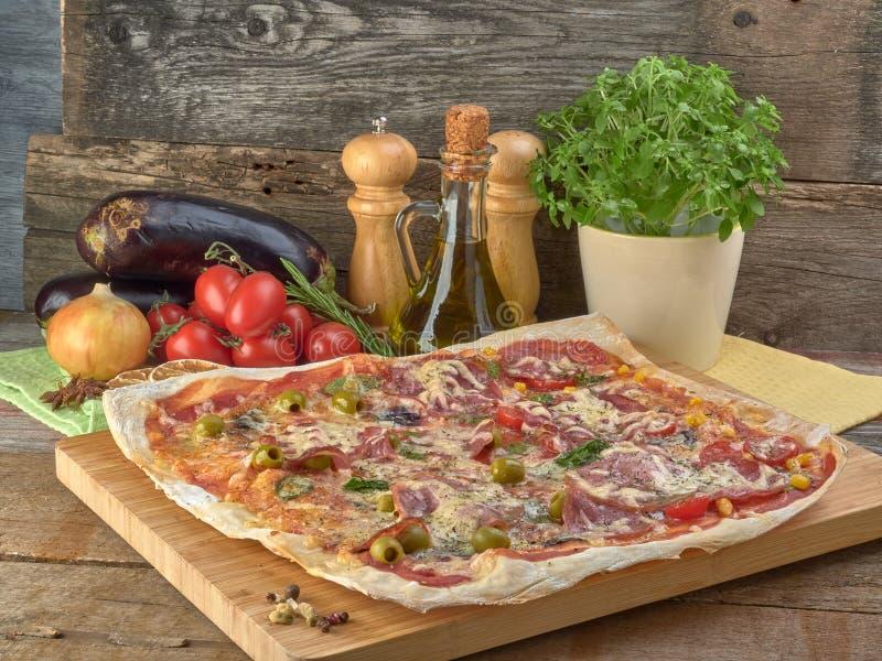 Pizza auf dünnem Teig Mit Scheiben der Salami und des Schinkens, der Oliven und der Tomaten lizenzfreie stockbilder