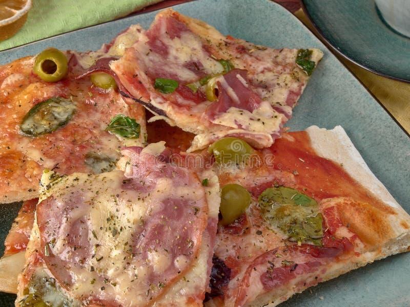 Pizza auf dünnem Teig Mit Scheiben der Salami und des Schinkens, der Oliven und der Tomaten lizenzfreie stockfotos