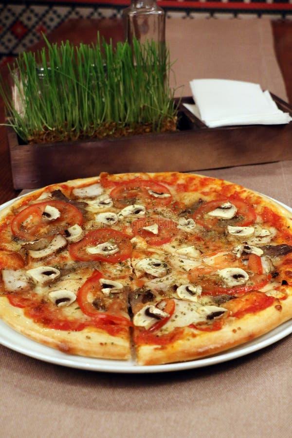 Pizza auf dem Tisch mit Geräten lizenzfreies stockfoto