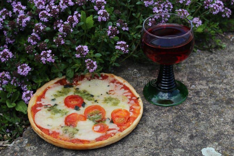 Pizza auf einem Thymianfeld und einem Rotwein lizenzfreie stockbilder