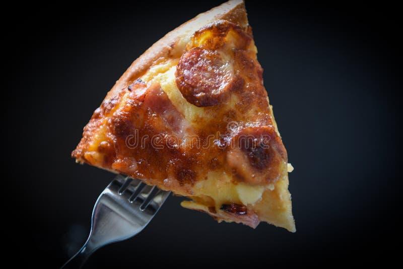 Pizza auf Gabel-/Scheibenpizzastück auf dem dunklen Schwarzen stockfoto
