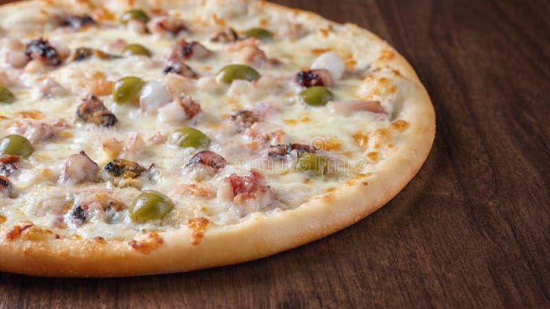Pizza avec des olives et des fruits de mer sur un plan rapproché en bois de table image stock