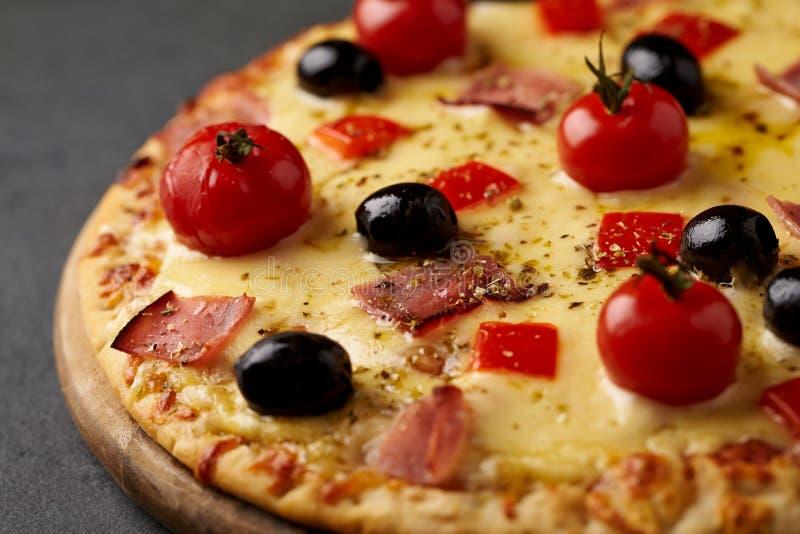 Pizza avec du jambon, le fromage de mozzarella, les tomates-cerises, le poivron rouge, les olives noires et l'origan La maison a  photo libre de droits