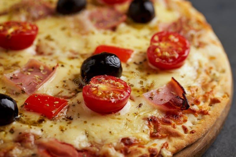Pizza avec du jambon, le fromage de mozzarella, les tomates-cerises, le poivron rouge, les olives noires et l'origan La maison a  image stock