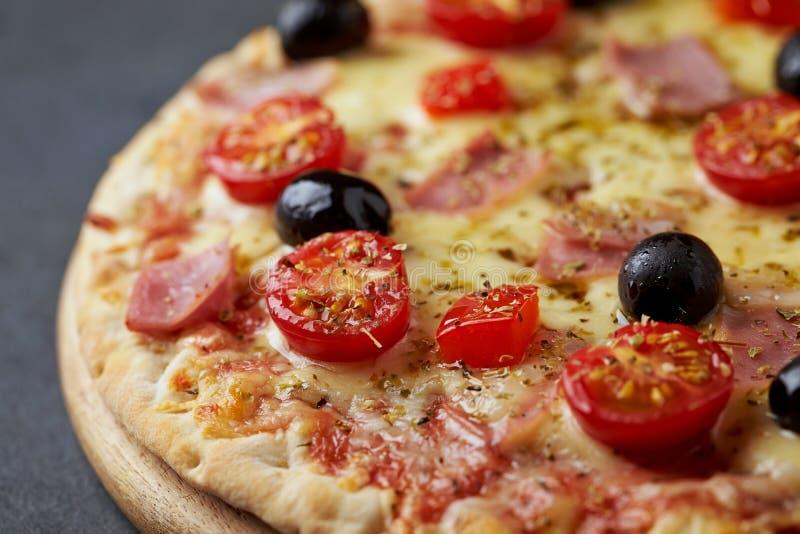 Pizza avec du jambon, le fromage de mozzarella, les tomates-cerises, le poivron rouge, les olives noires et l'origan La maison a  photographie stock