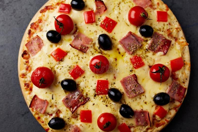 Pizza avec du jambon, le fromage de mozzarella, les tomates-cerises, le poivron rouge, les olives noires et l'origan La maison a  photos libres de droits