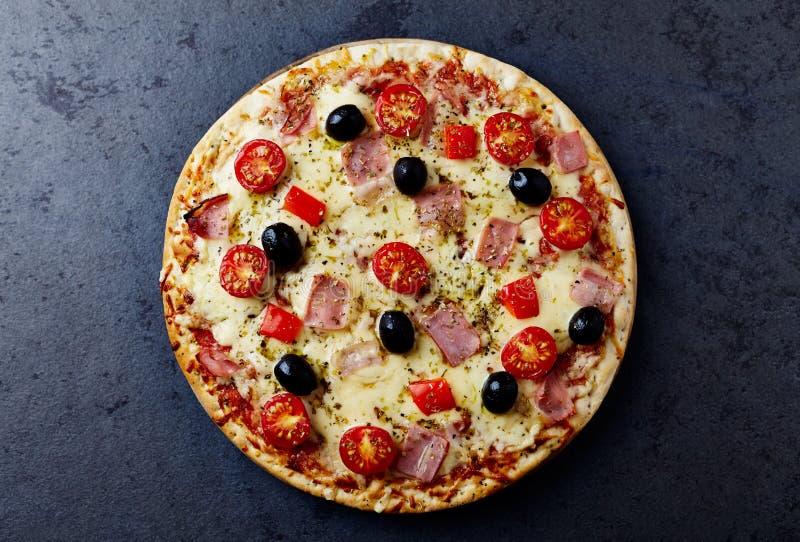 Pizza avec du jambon, le fromage de mozzarella, les tomates-cerises, le poivron rouge, les olives noires et l'origan La maison a  images libres de droits