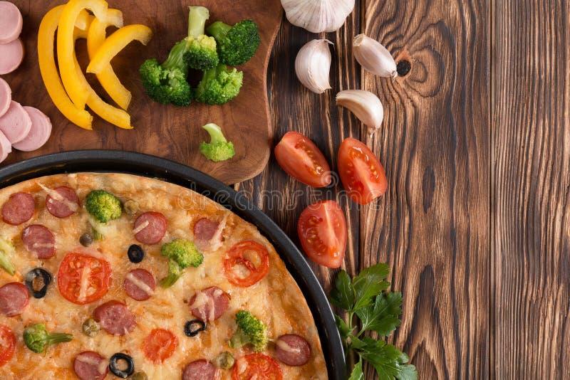 Pizza avec le brocoli, les pois, la saucisse, les olives, les poivrons et les tomates photographie stock libre de droits