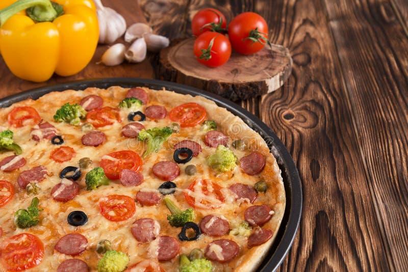 Pizza avec le brocoli, les pois, la saucisse, les olives, les poivrons et les tomates image libre de droits