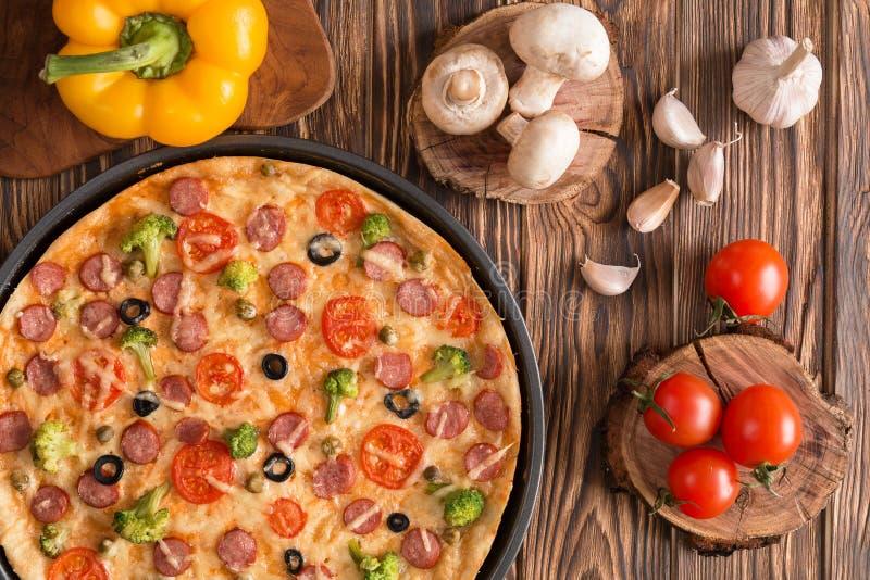 Pizza avec le brocoli, les pois, la saucisse, les olives, les poivrons et les tomates photo stock