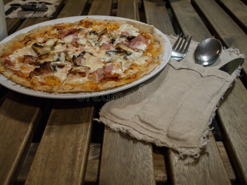 Pizza avec le lard et les champignons sur la table près de l'ensemble d'argenterie photographie stock libre de droits