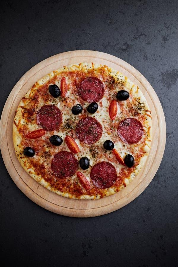 Pizza avec le salami, le fromage de mozzarella, les tomates-cerises, les olives noires et l'origan La maison a fait la nourriture photo libre de droits