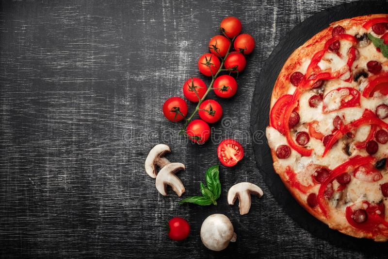 Pizza avec les saucisses fumées, le fromage, les champignons, les tomates-cerises, les paprikas et les verts sur une pierre photo stock