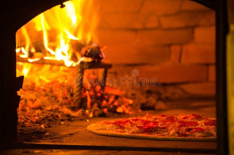 Pizza-Backen in Holz abgefeuertem Ofen lizenzfreies stockbild