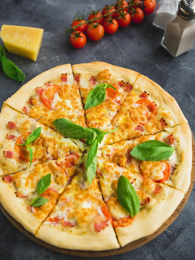 Pizza with bacon, cheese and tomato on dark background. Closeup view. Delicious food background royalty free stock photo