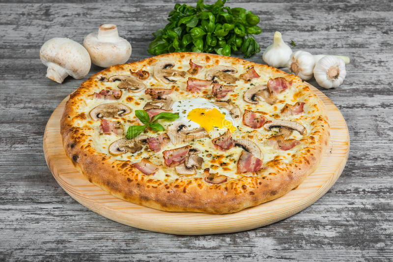 Pizza with bacon, mushrooms and egg, with rosemary and spices stock image