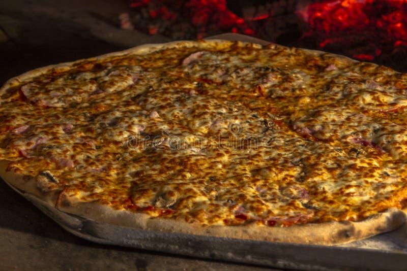 Pizza bakade i en stenpanna Mot en brinnande brand arkivfoto