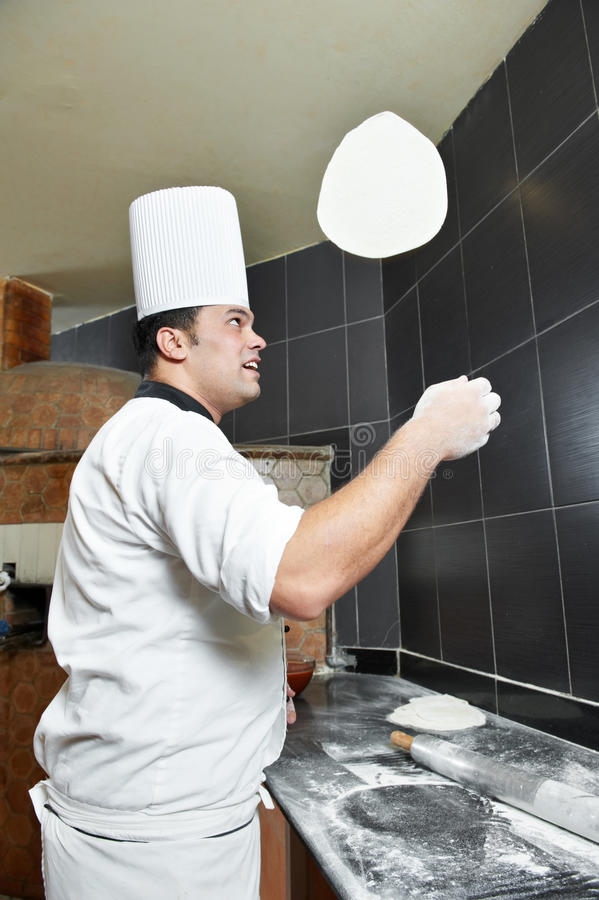 Pizza baker juggling with dough royalty free stock image