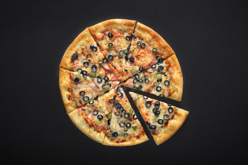 Pizza barbecue with cornichoni olives peperoni cheese mozzarella on black stone background royalty free stock images