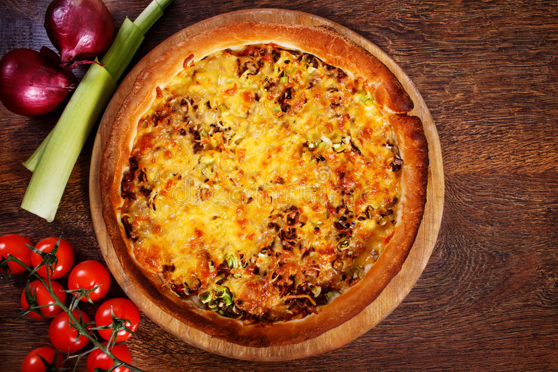 Pizza with beef stuffing, leek and cheese served on wooden table. Homemade pizza with thick crust royalty free stock images