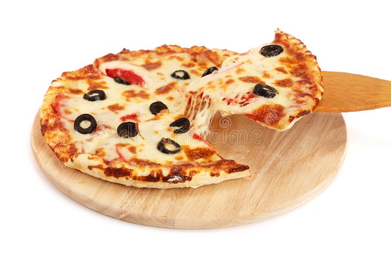 Pizza with black olives on a wooden board isolated on white background stock photography