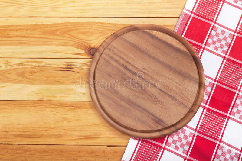 Pizza board with napkin on wooden table. Top view mockup stock image