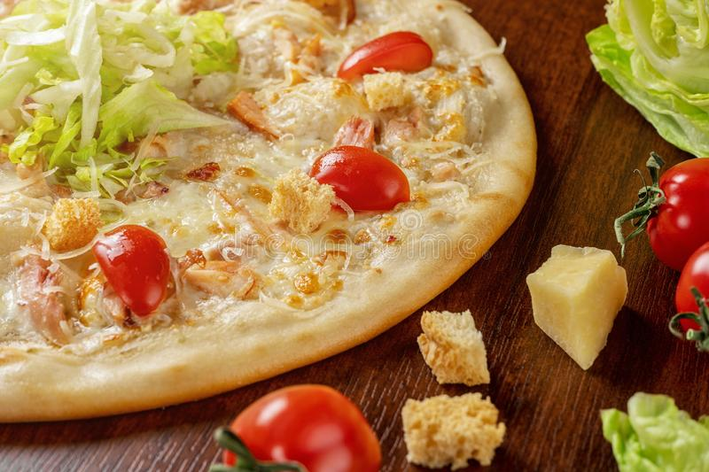 Pizza Caesar close-up on a wooden table next to tomato crackers and iceberg lettuce stock images