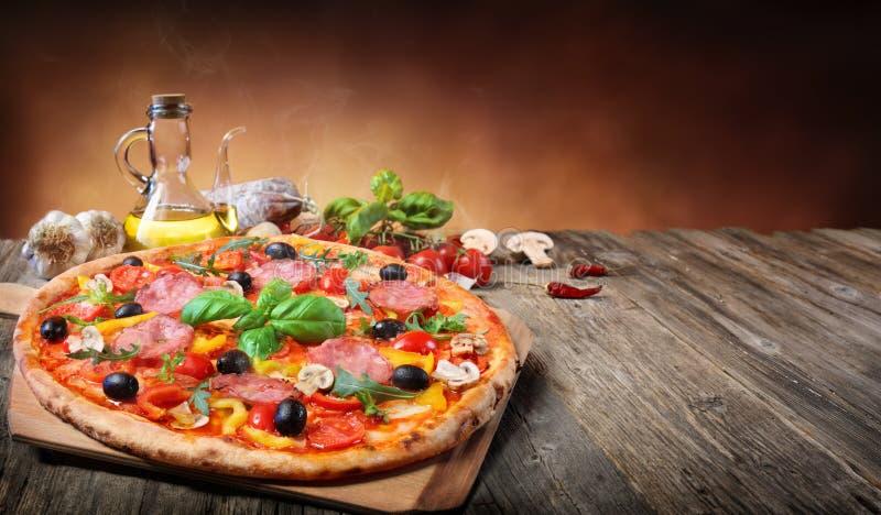 Pizza calda servita sulla vecchia Tabella fotografia stock