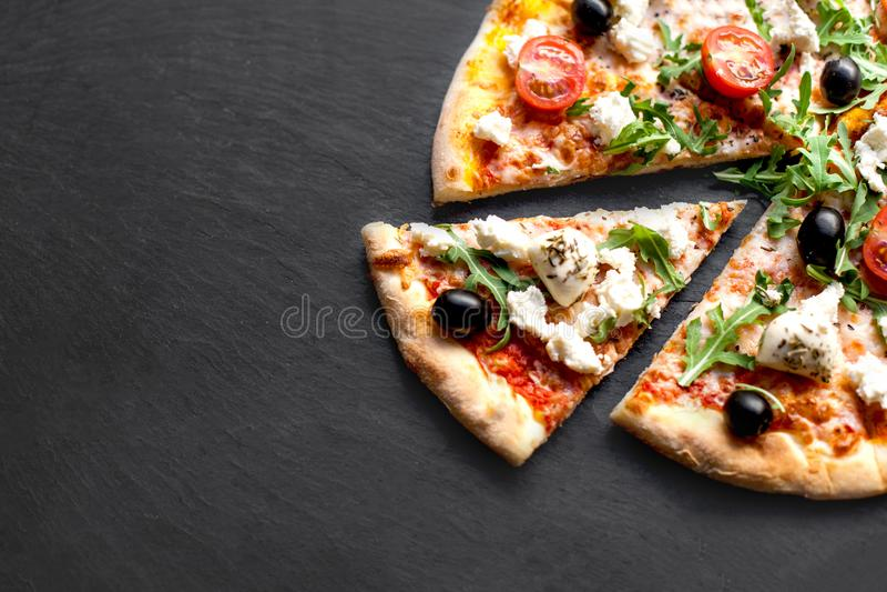 Pizza caliente cortada con los mariscos, el queso y las hierbas en backgr negro imagen de archivo libre de regalías