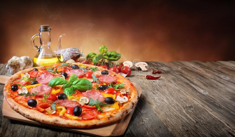 Pizza caliente servida en la tabla vieja fotografía de archivo