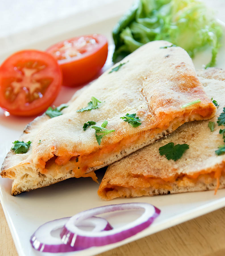 Pizza Calzone. With a fresh salad accompaniment on a white plate stock photography