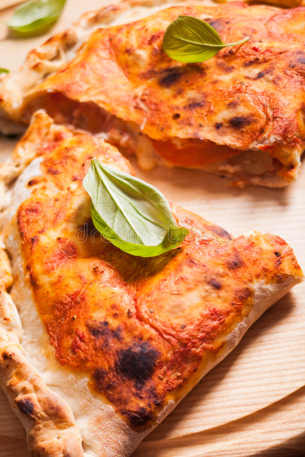 Pizza calzone. With basil leaves close up stock photo