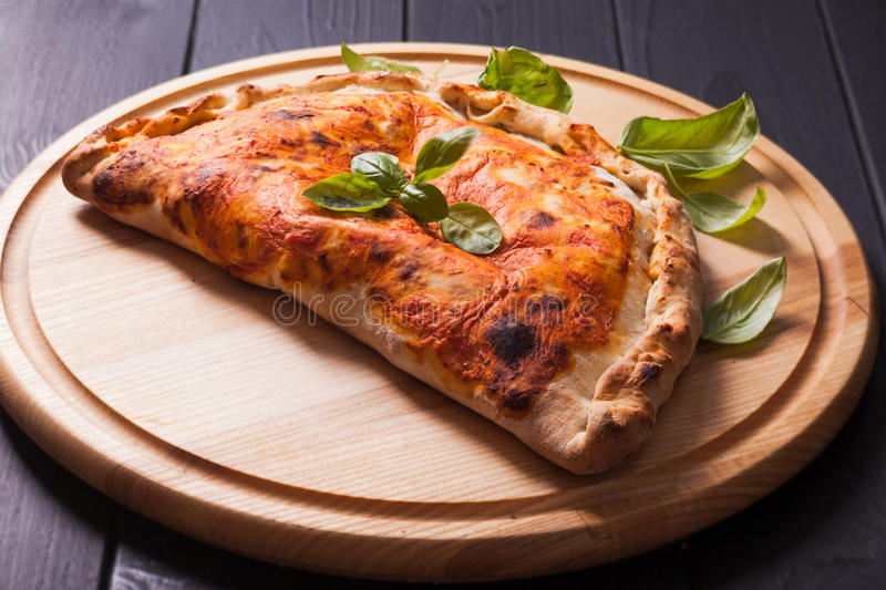 The Pizza calzone. Pizza calzone with basil leaves close up stock photography