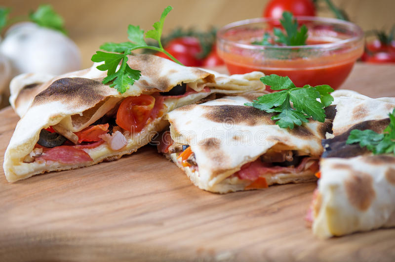 Pizza calzone with close up. Pizza calzone in the form of cutting with close up on a wooden background stock image