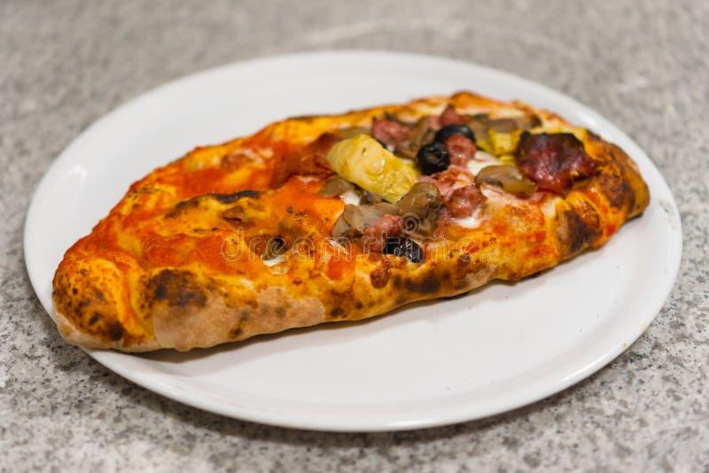 Pizza calzone. Calzone - Stuffed Pizza with Tomato, Mozzarella Ham and mushrooms royalty free stock image