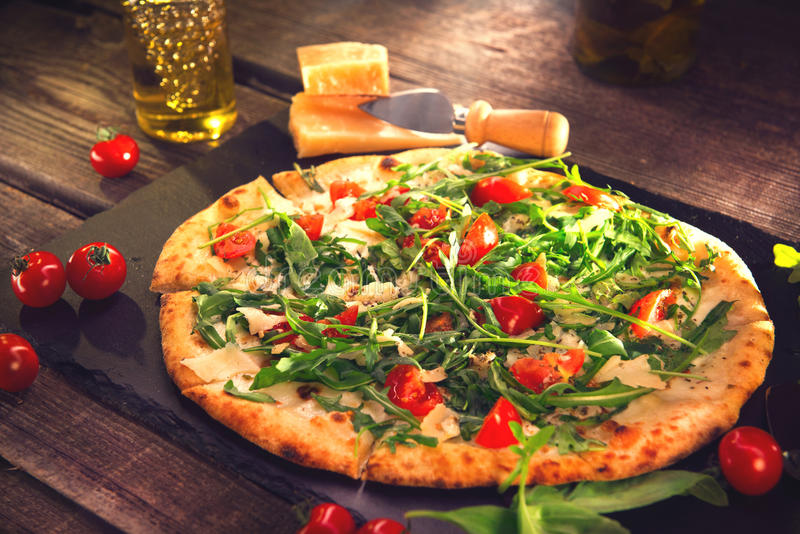 Pizza Caprese with arugula, cheese, yoghurt and cherry tomatoes. Homemade delicious vegetarian pizza on wooden table stock photography