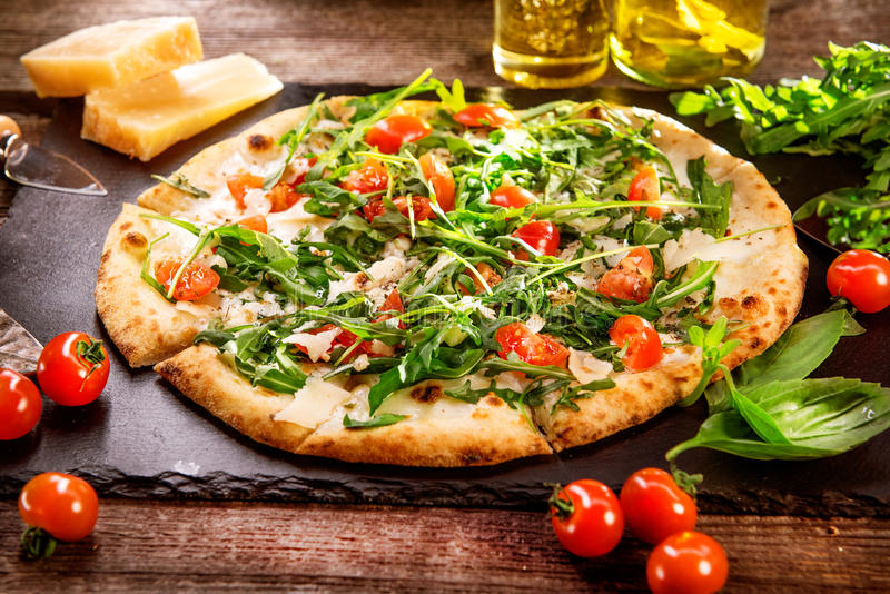 Pizza Caprese med arugula, ost, yoghurt och körsbärsröda tomater arkivbild