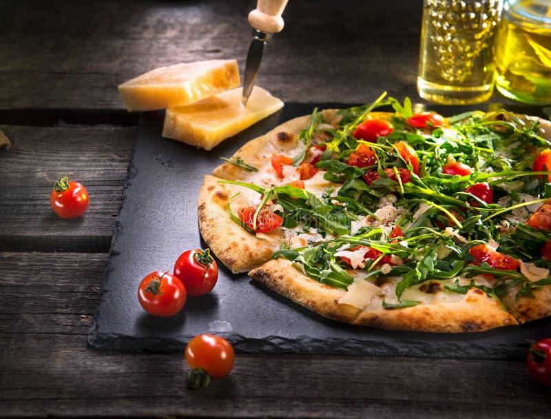 Pizza Caprese med arugula, ost, yoghurt och körsbärsröda tomater fotografering för bildbyråer