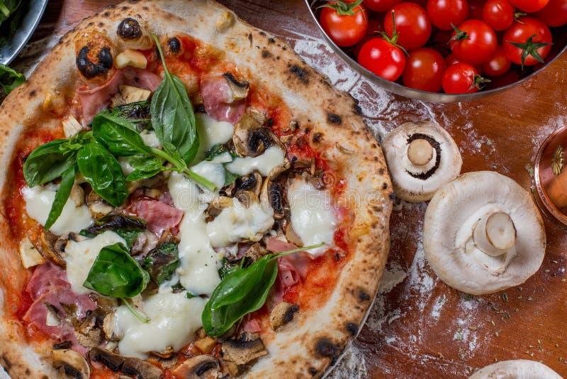 Pizza capricciosa with artichoke, ham and mushroom on wood background royalty free stock photo