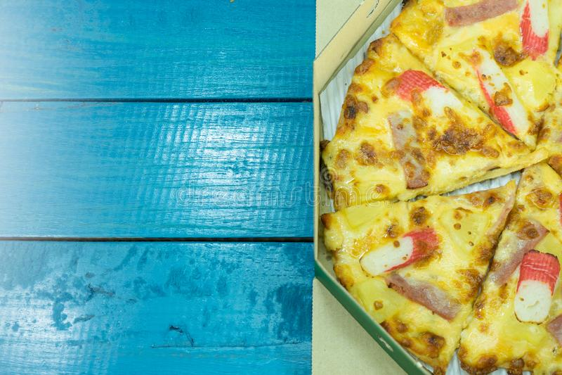 Pizza in cardboard on blue wooden table. royalty free stock photo