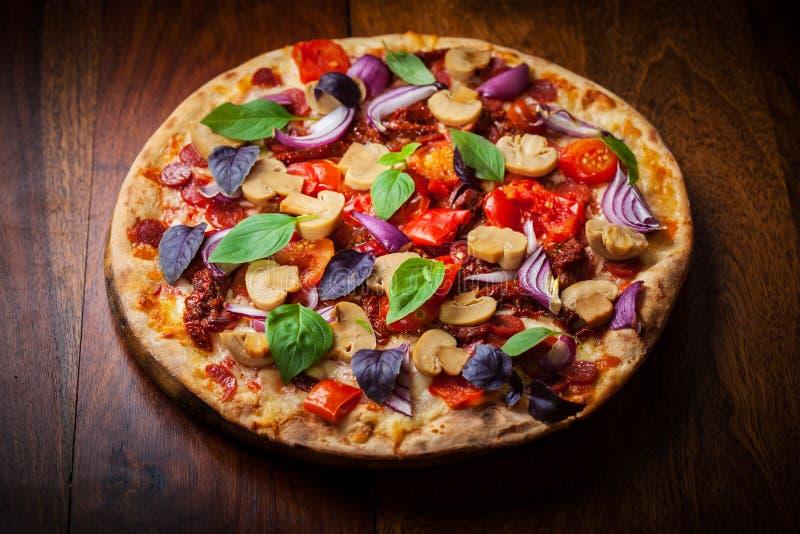 Pizza casalinga con i pomodori ed il salame secchi fotografia stock