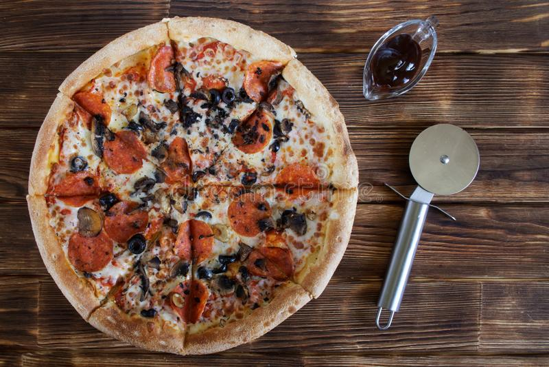 Pizza casalinga con le bugie del salame, dei funghi e delle olive su una tavola della plancia accanto ad una salsa speciale di pi immagini stock