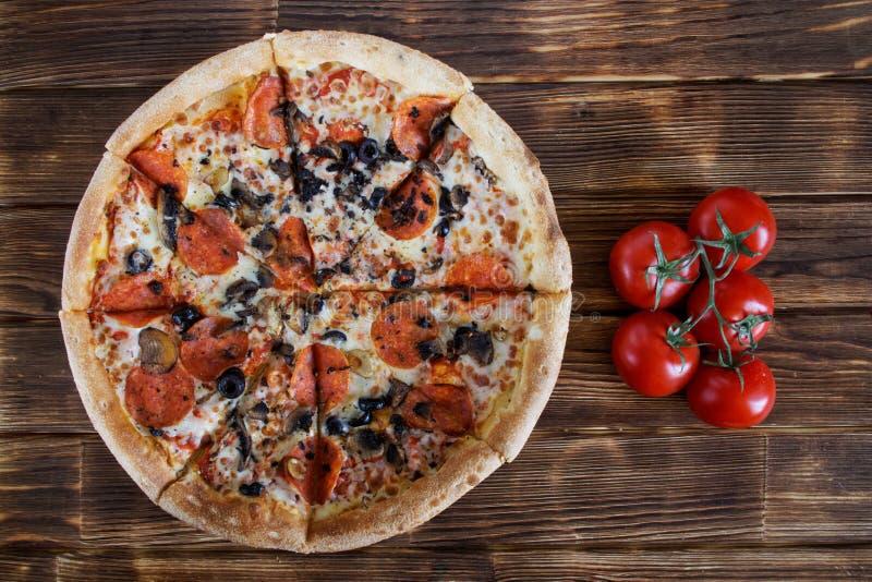 Pizza casalinga rustica con le bugie del salame, dei funghi e delle olive su una tavola di legno accanto ad un mazzo di pomodori  immagini stock