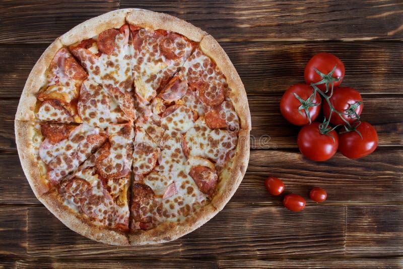 Pizza casalinga rustica con salame ed i lotti delle bugie del formaggio su una tavola di legno accanto ad un mazzo di pomodori ro fotografia stock libera da diritti