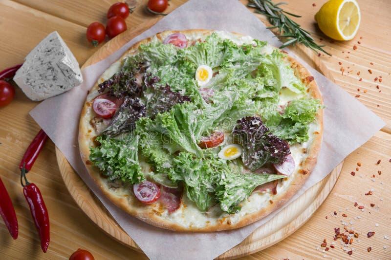Pizza caseiro com em um fundo de madeira com frutas e legumes com especiarias imagem de stock royalty free
