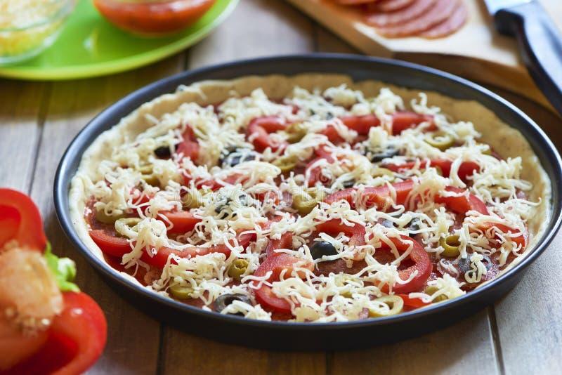 Pizza caseiro com pepperoni, pimenta e azeitonas Processo de cozimento Etapa 6 Queijo raspado adicionado imagem de stock royalty free